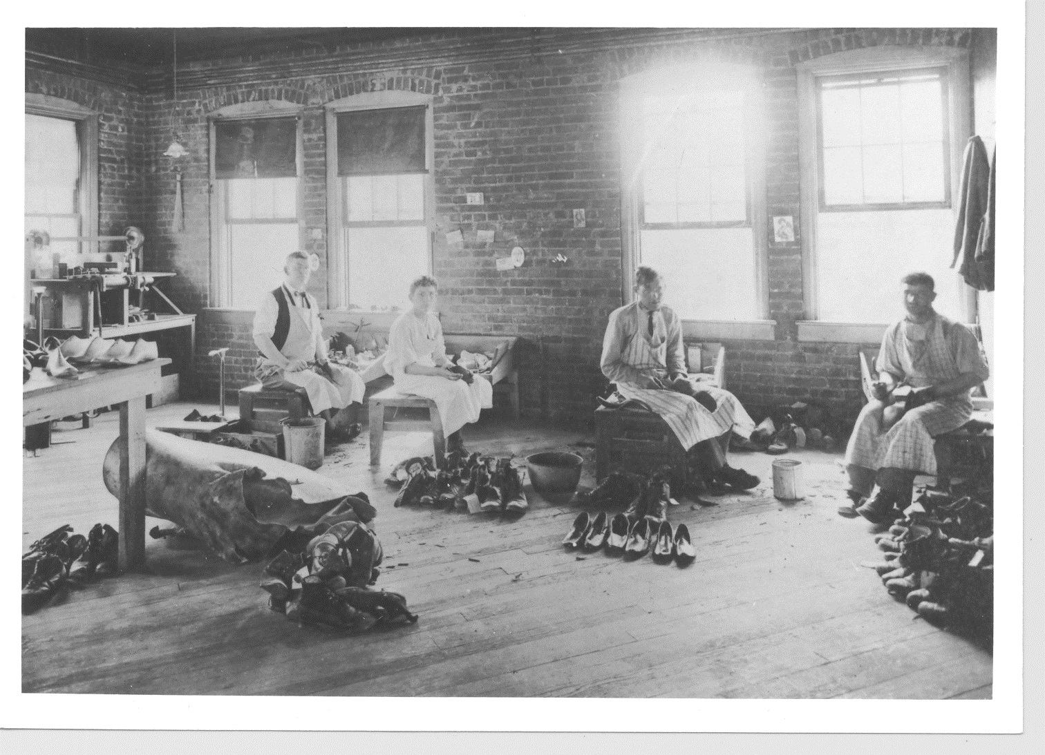 Image of men working in shoe shop at Craig Colony inside brick building