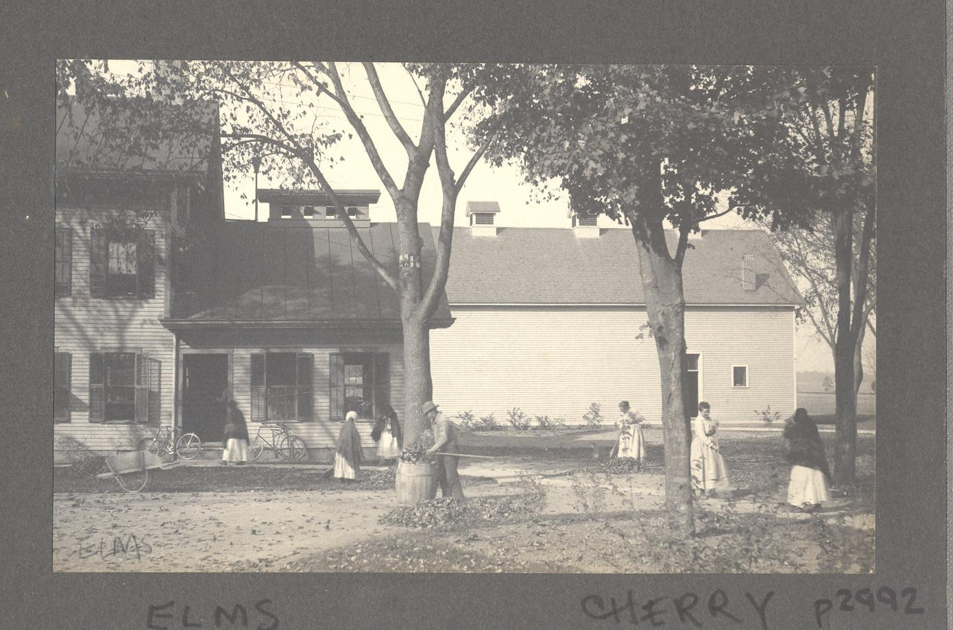 Image of Shaker buildings with men and women raking leaves in yard