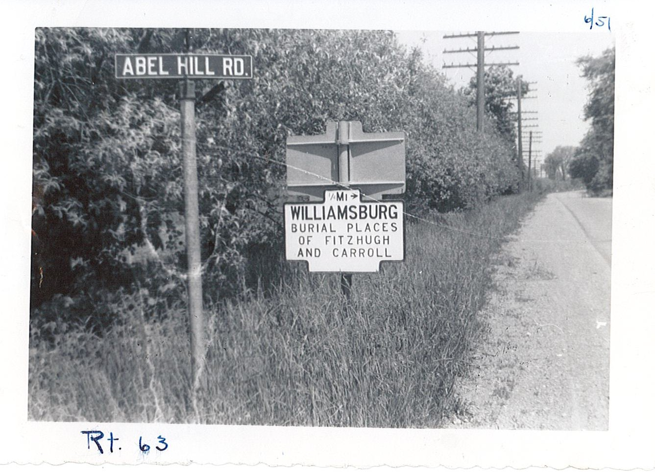 Image of blue and yellow historical marker sign for settlement of Williamsburg next to Abel Hill Road sign