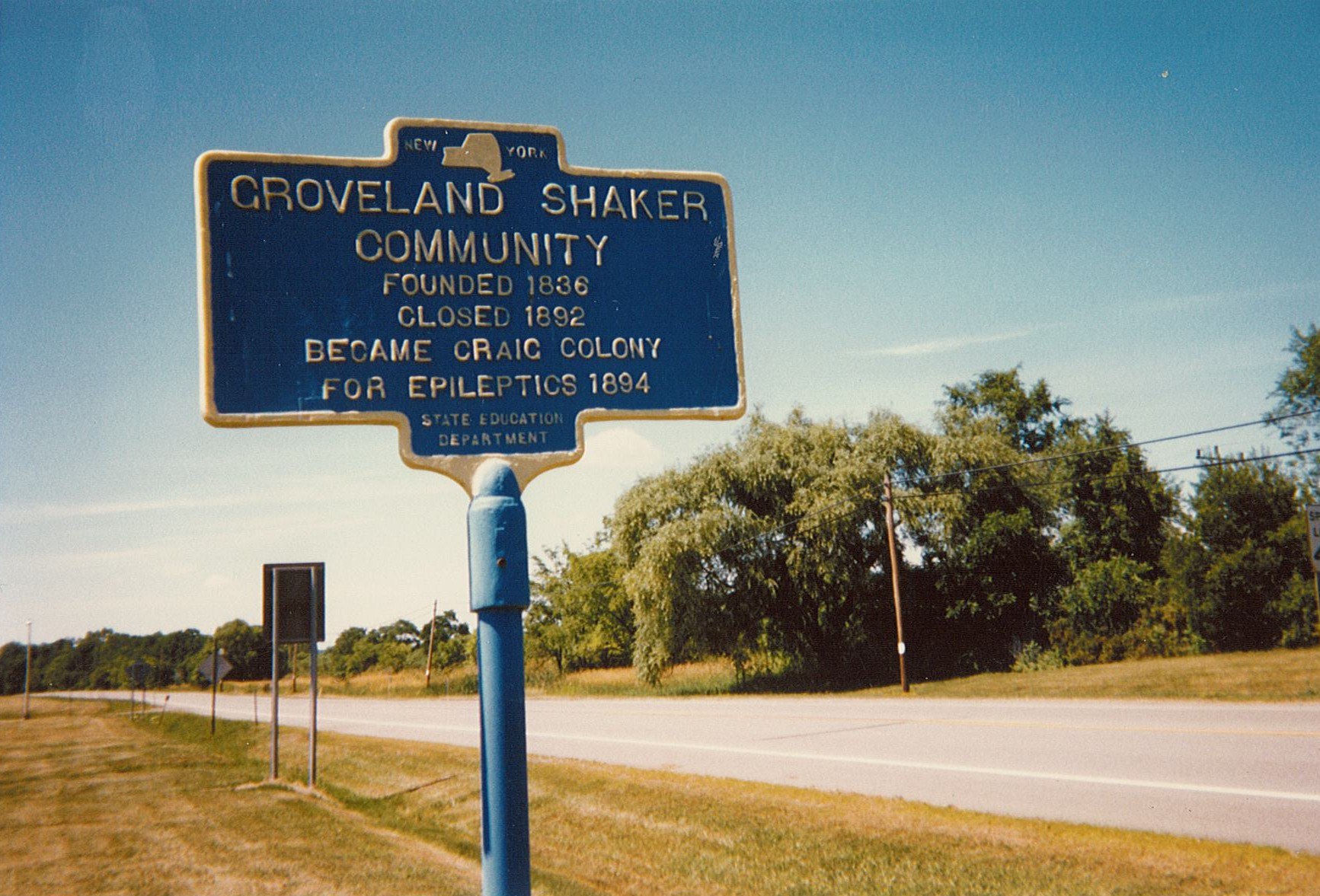 Image of blue and yellow historical marker sign for Groveland Shaker Community site