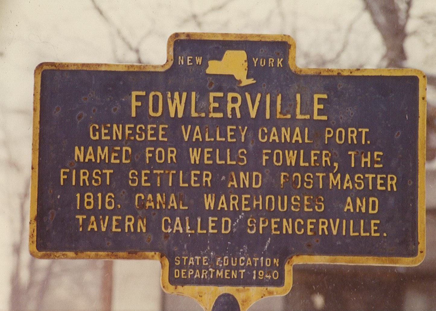 Image of blue and yellow historical marker sign for hamlet of Fowlerville